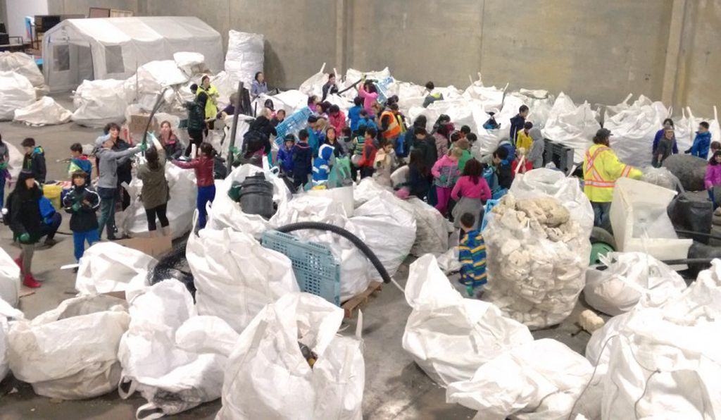 Volunteers with Ocean Legacy tackle sacks full of plastic marine debris at a warehouse in Vancouver.