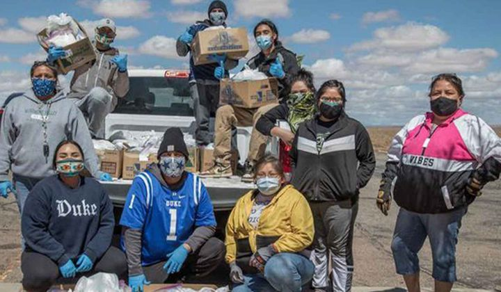 Volunteers with the Navajo & Hopi Families Covid-19 Relief Fund distribute food and other essential supplies to isolated communities and farmsteads on the Navajo Nation and Hopi Reservation. As part of the Smithsonian's virtual program 24 Hours in a Time of Change, Shandiin Herrera (Diné)—seated on the left, wearing a Duke University sweatshirt—describes how this grassroots response to the COVID-19 pandemic came together last spring and shares her experiences as the fund's volunteer coordinator in Monument Valley, Utah. (Photo by Karney Hatch)