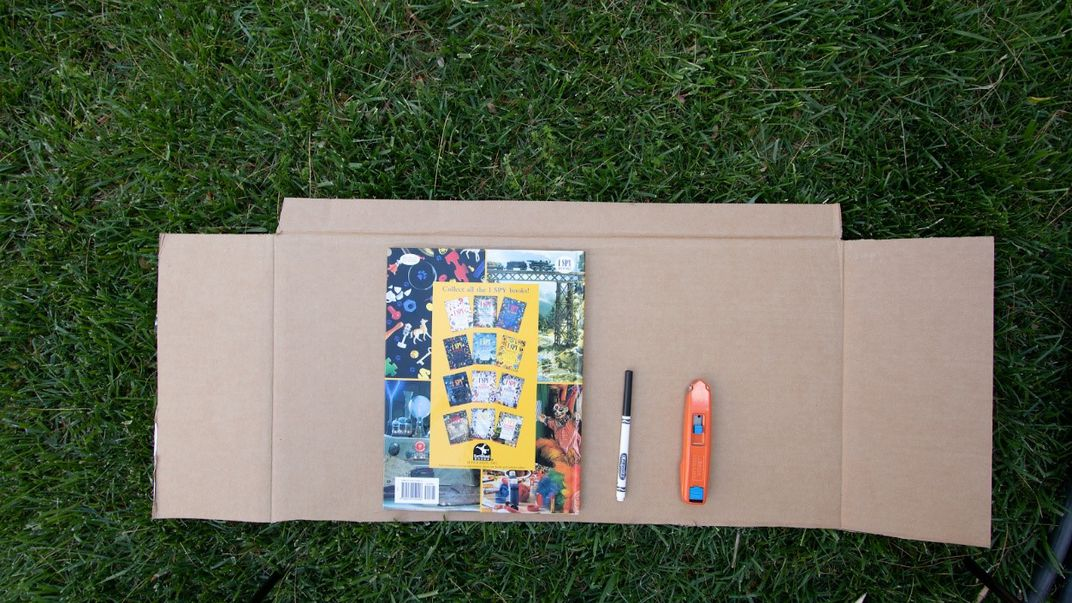 Book and marker on top of cardboard laying on grass.
