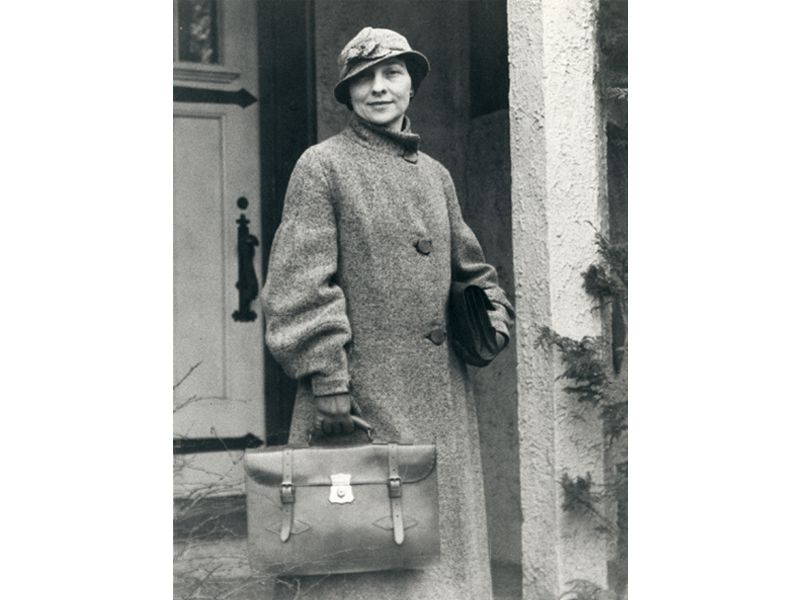 A young white woman in a long coat, wearing a fashionable hat cocked to one side on her head, carries a briefcase and poses in front of a doorway