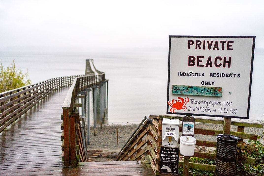 A sign in front of a dock stretching out into the water reads: PRIVATE BEACH. INDIANOLA RESIDENTS ONLY.