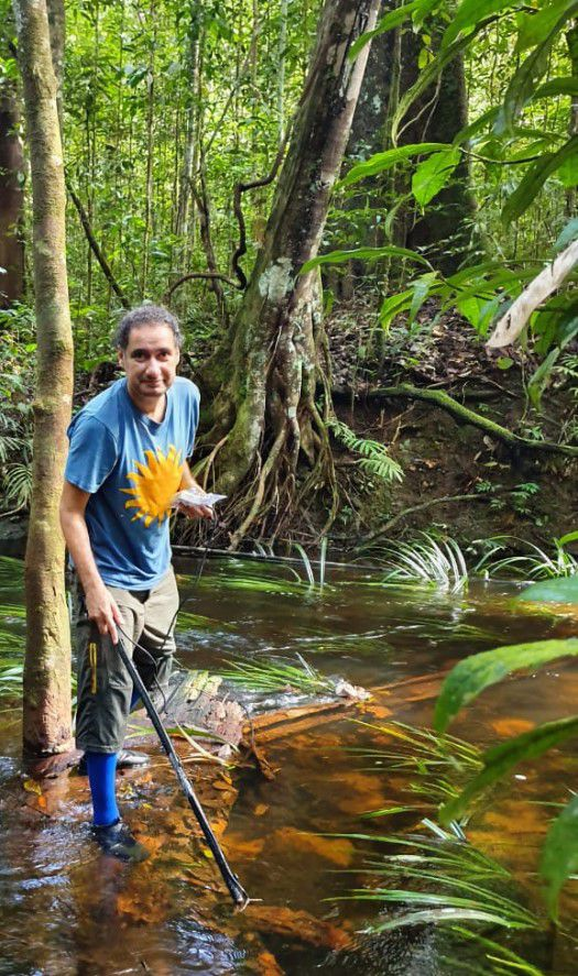 Smithsonian scientist David de Santana searching for electric eels in a river in the lush Amazon rainforest.