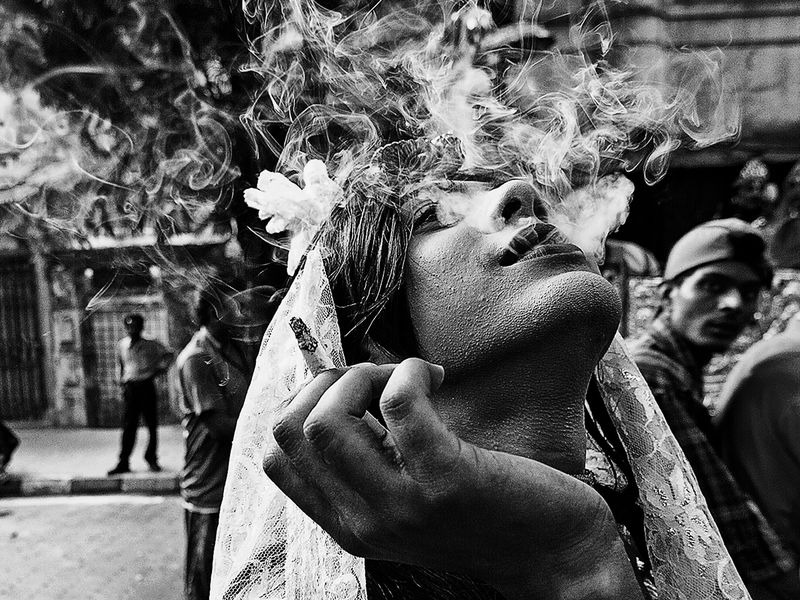 Gajon is a widely celebrated festival across India. People dresses themselves in different costume and perform rituals. In this picture, a transgender was smoking in the street and i was very lucky to get this picture.