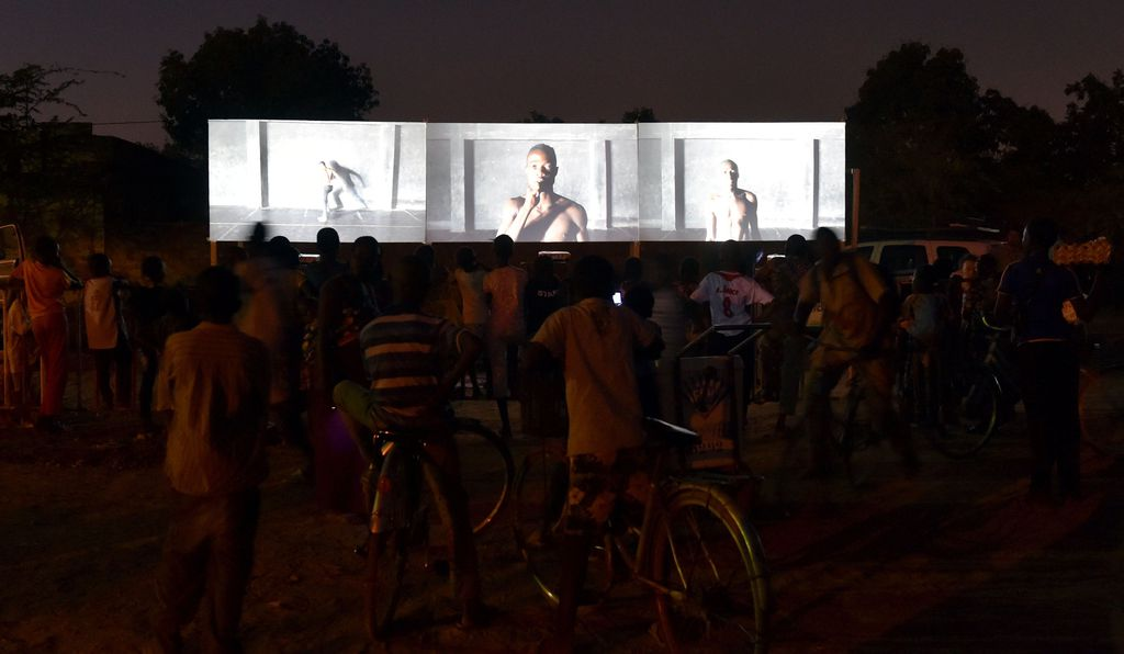 People on bikes stop to watch a documentary film shown at an open, outdoor screening during the 2017 Panafrican Film and Television Festival (FESPACO) in Ouagadougou.