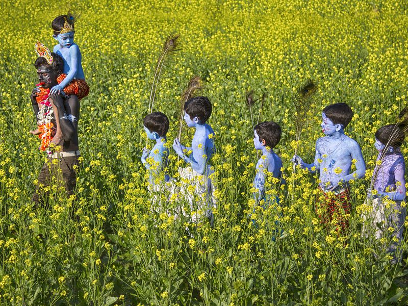 The little actors after dressed like lord Krishna and Goddess Kali  are on their way to a distant village where the drama will be held.
