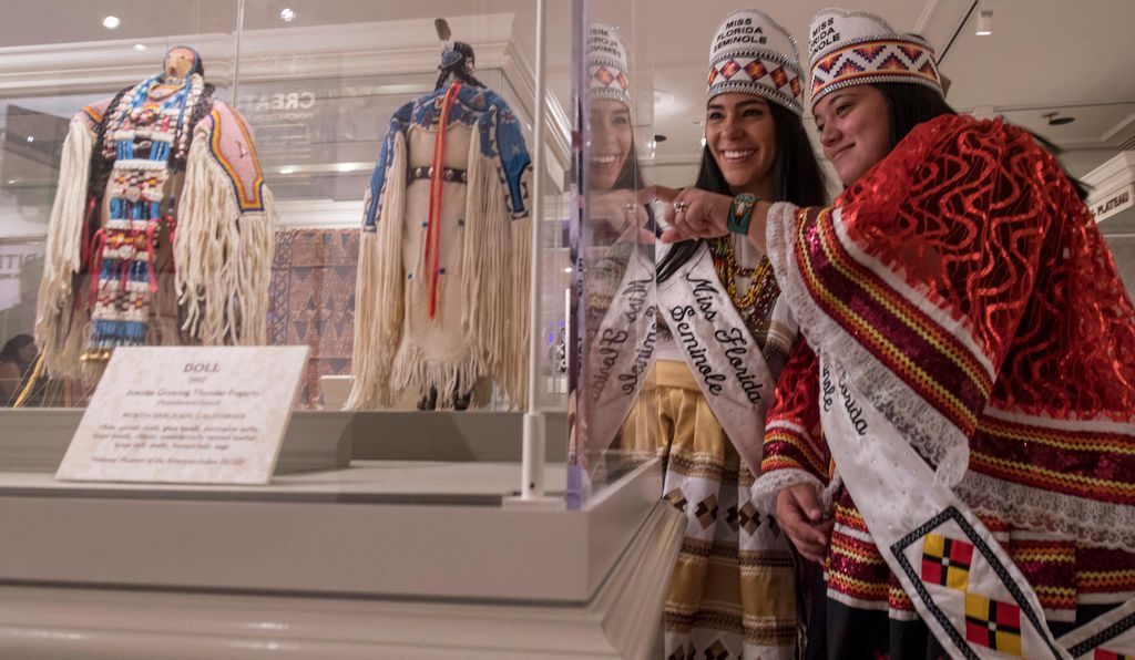 Miss Florida Seminole, Cheyenne Kippenberger, and Jr. Miss Florida Seminole, Allegra Billie, of the Seminole Tribe, admire dolls created by artists Juanita Growing Thunder and her grandmother, Joyce Growing Thunder, with the Assiniboine/Sioux tribes. Both dolls are on loan from the Smithsonian's National Museum of the American Indian.
