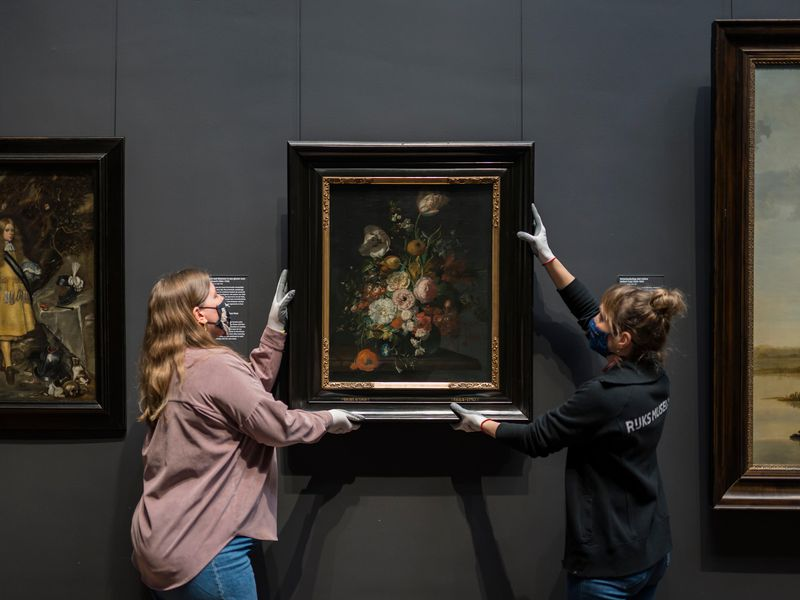 Two people in gloves and masks hold either side of the painting, which depicts a lush bouquet, and hangs it on the dark gallery wall