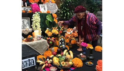 Doña Ofelia Esparza decorates the ofrenda