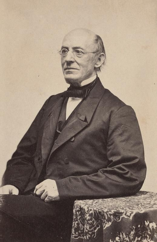 A sepia-toned image of an elderly man, with a bald crown and glasses, in a suit, seated with his hand resting on a small table and in front of a blank white background