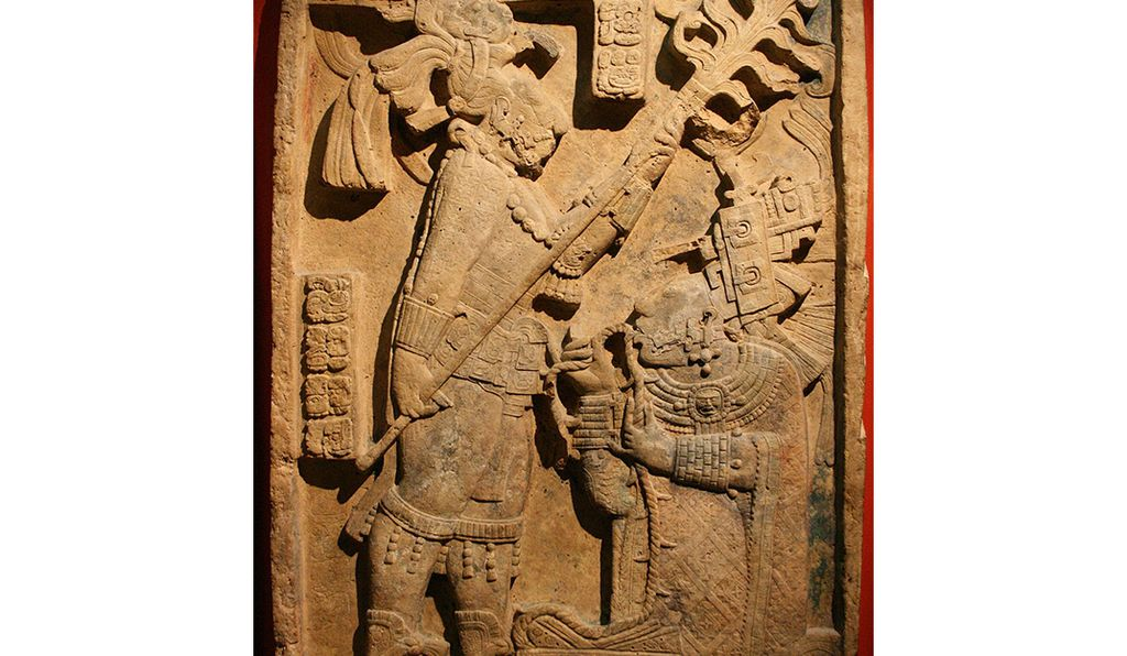 A carving depicting Lady K'ab'al Xook, wife of king Shield Jaguar II, drawing a barbed wire through her tongue. The carving, found in the Yaxchilan,Mexico, resides at the British Museum.