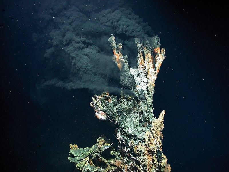 A hydrothermal vent in the deep ocean produces a dark, cloud of hot air against a dark blue background. The vent in the foreground is rocky, like a conglomerate of shells and rocks piled on top of each other.