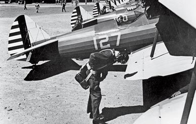 Man wearing a parachutes next to a plane during WWII.