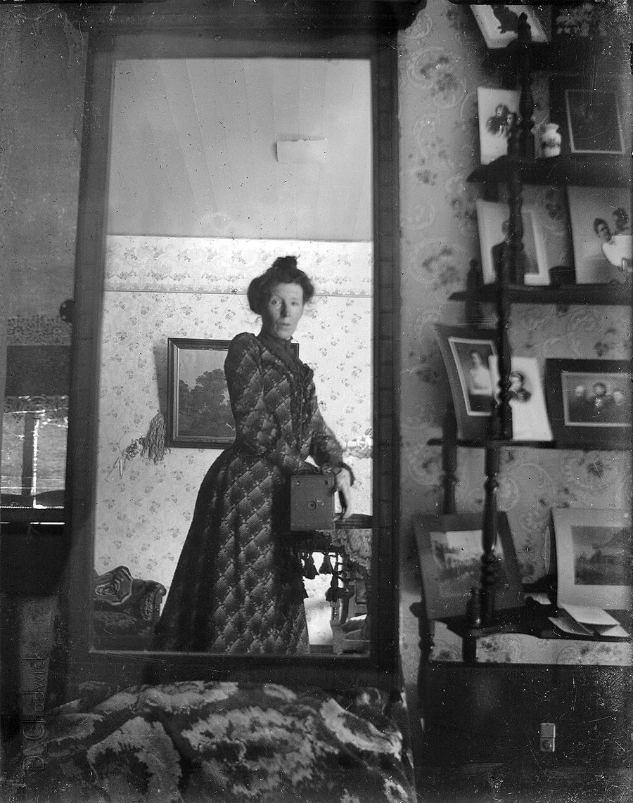 Unidentified_woman_taking_her_own_photograph_using_a_mirror_and_a_box_camera,_roughly_1900.jpg