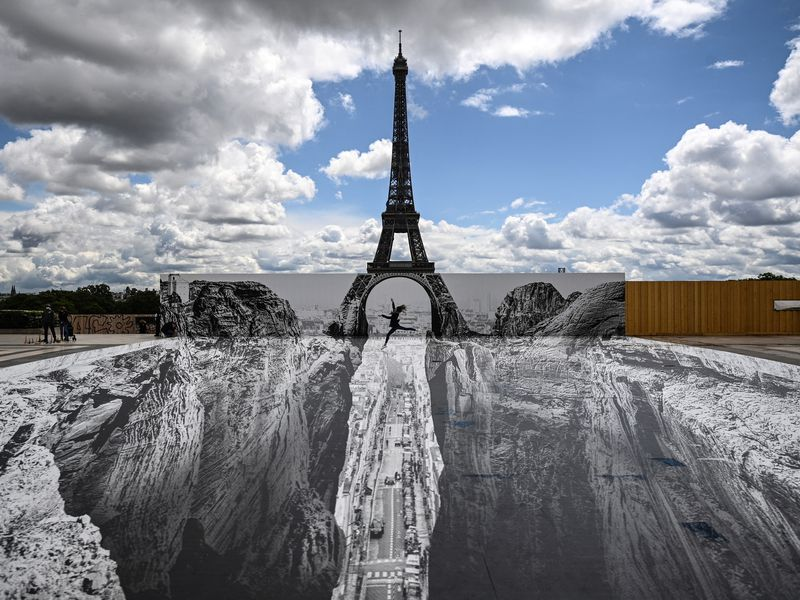 JR's latest illusion seemingly opens up a ravine in front of the Eiffel Tower